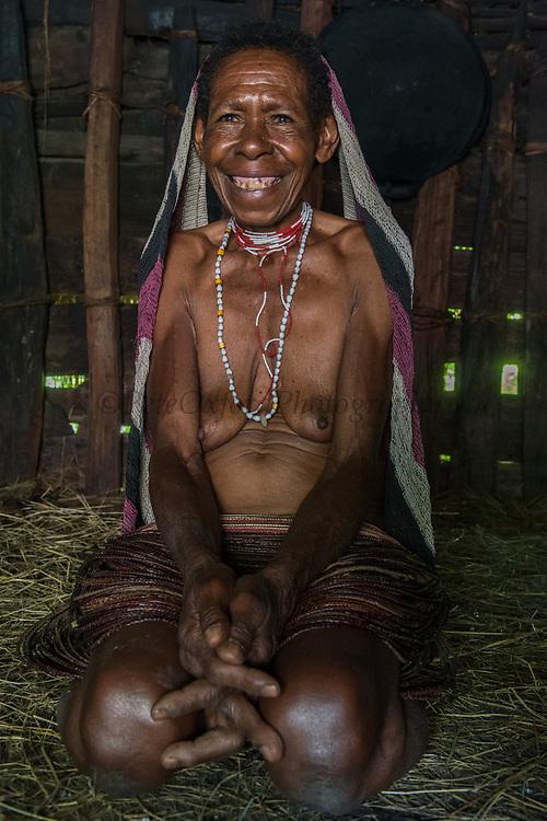 Dani tribe woman inside<br /> Budaya village<br /> Suroba<br /> Trikora Mountains<br /> West Papua<br /> Indonesia<br /> Inside hut