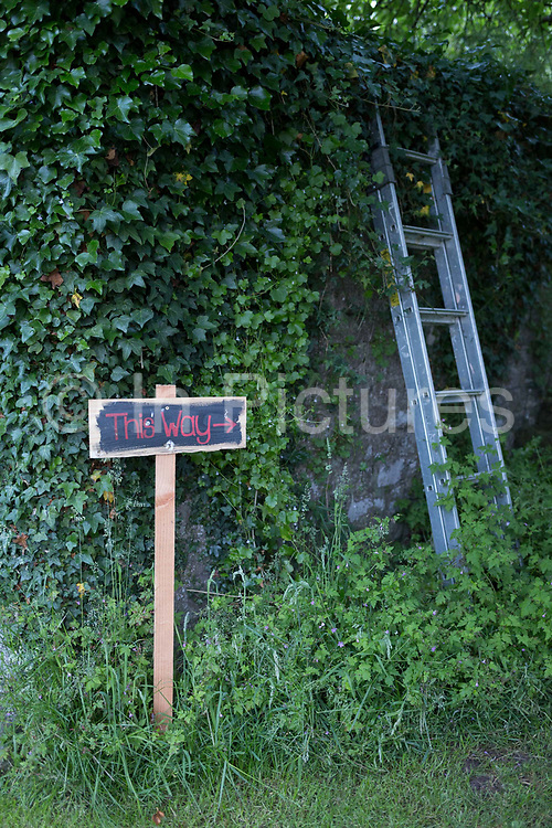 A hand-painted sign showing guests where to proceed before a 50th birthday party in the Herefordshire countryside garden, on 23rd June 2019, in Kington, Herefordshire, England.