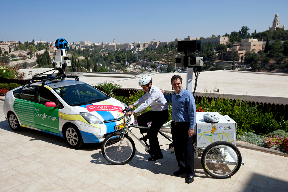 """A Google Street View car is displayed as Mayor of Jerusalem Nir Barkat (C), rides a Google Street View tricycle and Google Israel, South Africa & Greece managing director Meir Brand (R) stands next to him, following a press conference in Jerusalem, Israel, on September 12, 2011, in which Google has announced it will begin collecting images in Israel for the """"Street View"""" feature in Google Maps. In the coming weeks, Israel will join more than 30 other countries around the world which operate Street View, as Google cars and tricycles will begin driving and taking 360-degree photographs of streets, tourist destinations and other locations around the country. Images collected by the cameras mounted on vehicles will be processed and carefully stitched together to allow users to explore virtually and navigate cities, neighborhoods, streets and sites through panoramic street-level images."""