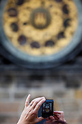 A tourist taking a photograph of the Prague astronomical clock, or Prague orloj which is a medieval astronomical clock located at Old Town Square in the capital of Czech Republic.