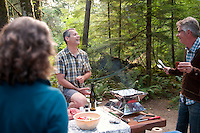 A group cooks a gourment dinner on a portable barbeque while camping at BC Parks Elk River Falls Provincial Park.