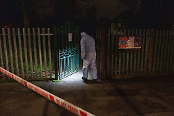 © Licensed to London News Pictures. 20/01/2020. London, UK. A forensic investigator searches for evidence at the entrance to a park. Police cordoned off a road & park and searched a property approximately half a mile from the location where an investigation was launched into the deaths of three men in Redbridge, all of whom had suffered apparent stab injuries.. Photo credit: Peter Manning/LNP