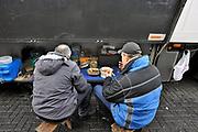 Nederland, A1, Losser, 24-1-2017Op een parkeerplaats aan de grens staan verschillende vrachtwagens uit diverse landen van Europa, met vooral chauffeurs uit Polen en andere oost europese landen. De chauffeurs nemen hun verplichte rusttijd, of melden zich bij het kantoor van de douane om hun papieren van de lading te laten zien. Een chauffeur en bijrijder uit Wit-Rusland eten hun maaltijd nij de truck.In a parking lot are several trucks from various countries of Europe, especially from the new countries, eastern europe. The riders take their mandatory rest period.~Foto: Flip Franssen