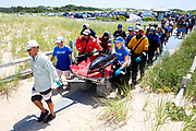 An atlantic white-sided dolphin is transported by a team of rescuers from the International Fund for Animal Welfare (IFAW) while being released back into Cape Cod waters at Herring Cove Beach in Provincetown, MA The dolphin is one of 14 that stranded in Black Fish Creek, Wellfleet earlier today. Ten dolphins were successfully released.