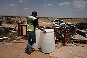 Leon Curley fills barrels at a residence in the heat of the day near White Rock in the Navajo Nation.