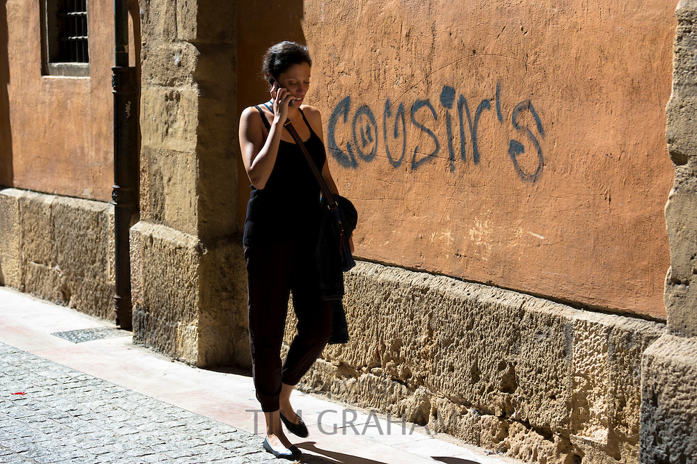Spanish woman using cellphone in Calle Sacramento in Leon, Castilla y Leon, Spain