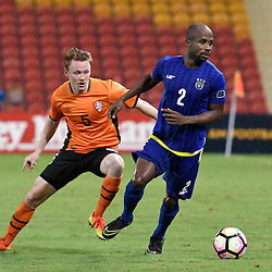 BRISBANE, AUSTRALIA - JANUARY 31: Serge Kaole of Global FC dribbles the ball under pressure from Brisbane Roar Defender Corey Brown during the second qualifying round of the Asian Champions League match between the Brisbane Roar and Global FC at Suncorp Stadium on January 31, 2017 in Brisbane, Australia. (Photo by Patrick Kearney/Brisbane Roar)