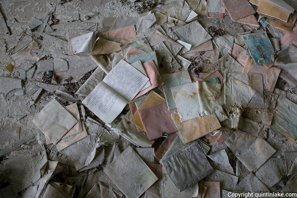 Exercise books and broken glass on a classroom floor.