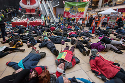 "© Licensed to London News Pictures. 15/12/2018. Bristol, UK. Campaigners stage a ""Die In"", part of the 'Extinction Rebellion' campaign event ""Bristol Rebellion Day"" to draw attention to the catastrophic impact of the fast-fashion industry and Christmas on our climate and ecological systems, part of a national day of action in many towns and cities about the threat of climate change. Regional Extinction Rebellion groups are taking part non-violent action to put pressure on local councils to transform policy in line with national demands to act on climate change. Campaigners say Bristol City Council is leading the way, having declared a climate emergency in November. Campaigners gathered inside Cabot Circus on the bottom floor, with songs from the XR Choir and a die in where all activists will lay on the floor. The campaign wants to make ecocide a crime in UK law, saying the threat of climate change threatens the lives of millions of people on the planet. The campaign is organised by Rising Up. Photo credit: Simon Chapman/LNP"