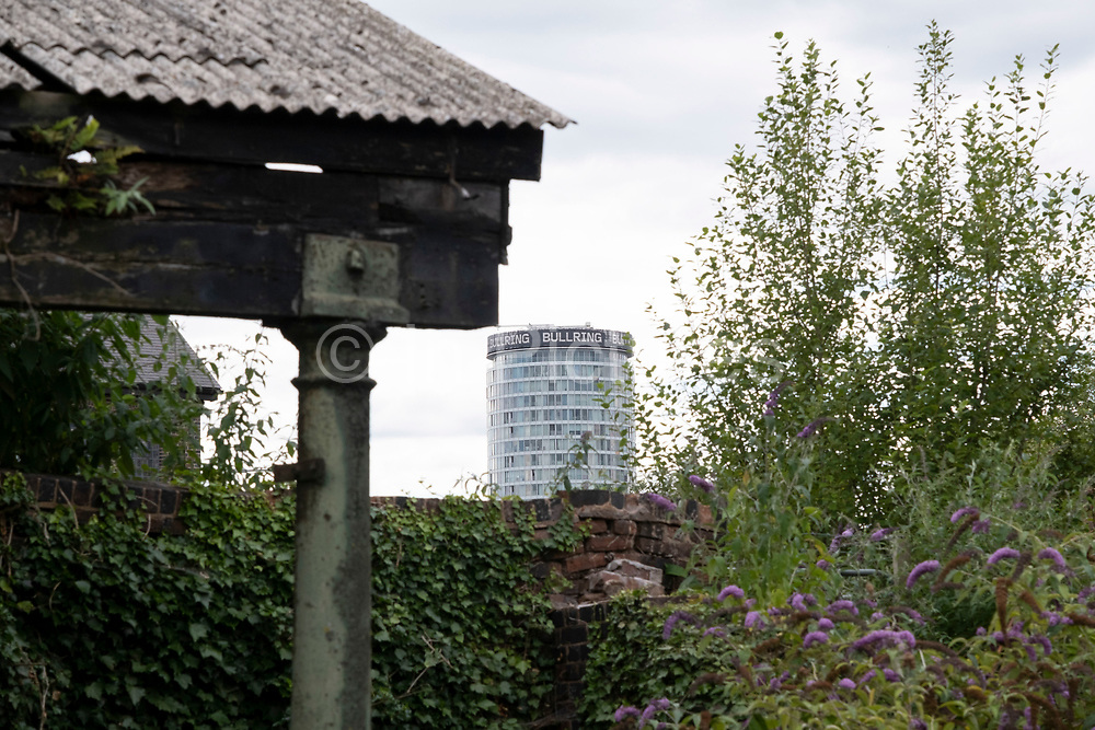 Scene along the Grand Union Canal, very close to the city centre where old, crumbling buildings provide a foreground to a modern city and the iconic Rotunda building on 3rd August 2020 in Birmingham, United Kingdom. Birmingham has around 35 miles of canals, said to be more than in Venice, and are very much a reminder of a Birminghams industrial heritage. During the Industrial Revolution these canals were busy, transporting heavy goods like coal, iron, while playing a pivotal role in the development of Birmingham as an industrial powerhouse.