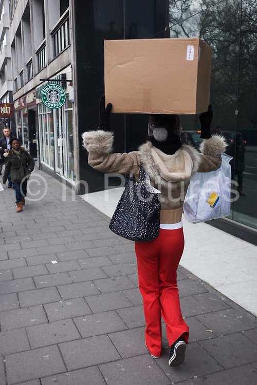 A young woman carries a cardboard box, balanced on her head as she walks along a central London street. Wearing bright red trousers, the woman manages to carry the box expertly as she walks down Piccadilly, a main street in central London. With handbags perched on both shoulders and making her way towards more pedestrians, the lady continues her way to her destination. It is too large to carry in front of her and has decided to manhandle it as she may have seen in developing countries, such as Africa.