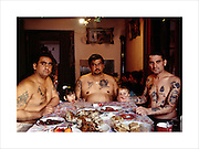 David, his brother and brother in law, at the dinner table for Orthodox Catholic Christmas meal. Joined by his grandchildren, but the woman in true Roma tradition do not join the men at the table.  Belgrade, Serbia January 7th, 2004..Roma Gypsies left Rajasthan in India a thousand years ago, in the ninth and tenth centuries. They were pushed west by the Ottoman Muslim Empire as it moved through Persia towards the frontiers of Europe. They entered Europe in the foutrteenth century and were slaves in Romania and Moldavia until the mid 1850s. There are about 15 million Roma gypries in the world, about 12 million who live in Europe. they are Europe's largest ethnic minority. They have rich traditions and culture, their own language. They are renowned for their prowess in music and dance; they are also skilled craftsman, metal roofmakers, silver and goldsmiths. Their traveling and nomadic lifestyle which grew from a necessity to find work, and because they were often moved on from one place to the next, has given them both a liberty but also marks them as different and they are often feared by sedentary peoples, who label and scapegoat them. They are hardy survivors and live in the brunt of racism and prejudice, often marginalised, living in poverty, without proper human rights afforded to them..