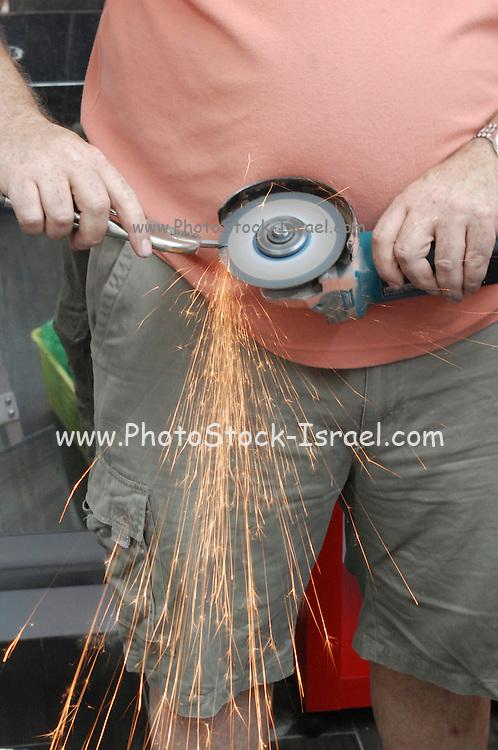 Handyman sharpens a drill bit