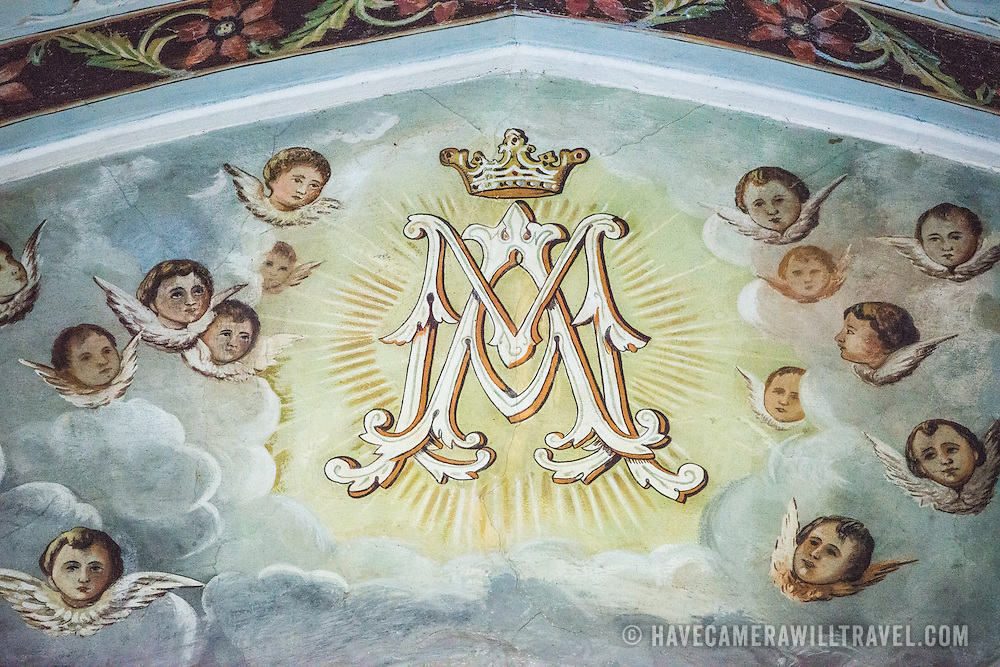 Paintings on the upper walls of La Capilla Maria Auxiliadora. La Capilla Maria Auxiliadora is located in the western part of Granada and features a lavishly decorated interior with walls in pastel blue and green.