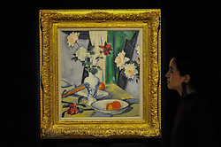 """© Licensed to London News Pictures. 17/11/2017. London, UK.  London, UK.  17 November 2017.  A staff member views """"Still Life of Roses with a Blue and White Vase"""", by Samuel John Peploe (Est. GBP 350-550k).   Preview upcoming auctions of Modern & Post War British Art and Scottish Art taking place at Sotheby's, New Bond Street, on 21 and 22 November. Photo credit: Stephen Chung/LNP"""