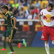 Jonny Steele, (left), New York Red Bulls, stands dejected as Maximiliano Urruti. Portland Timbers, celebrates after scoring the first of his two goals during another New York Red Bulls loss in their 2-1 home defeat against the Portland Timbers during the Major League Soccer regular season match at Red Bull Arena, Harrison, New Jersey. USA. 24th May 2014. Photo Tim Clayton