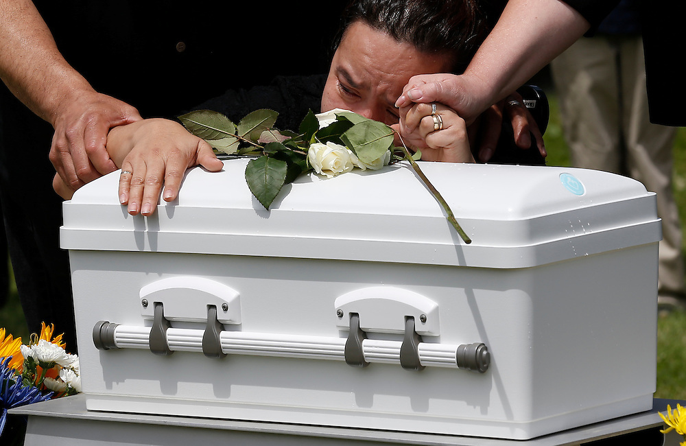 """The grandmother of baby Angel Antonio cries on his casket during a burial service at All Saints Cemetery in Des Plaines, Illinois, United States, June 19, 2015. More than a year after he was found dead in a plastic shopping bag on a Chicago sidewalk, the baby boy was buried by a non-profit group """"Rest in His Arms"""" after being abandoned by his teenage mother, who is charged with murder. Picture taken June 19, 2015. <br /> REUTERS/Jim Young"""