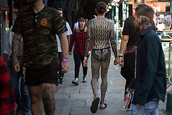 People show off their tattoos during the International tattoo convention at Tobacco Dock in east London.