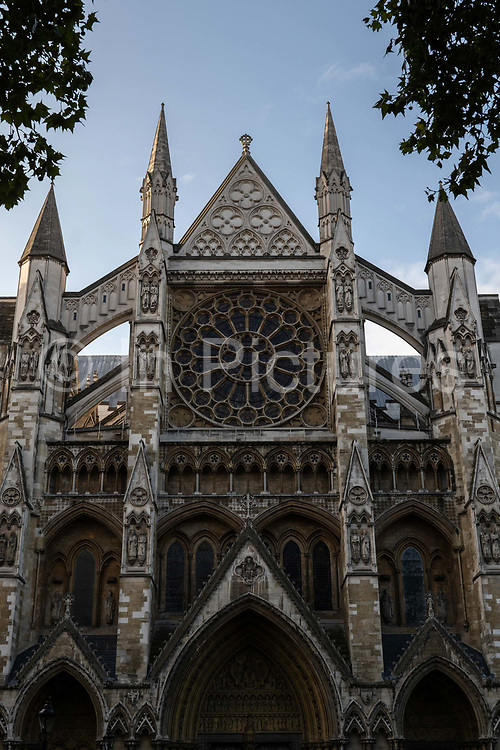 Early morning light on Westminster Abbey with the Winston Churchill Statue in the foreground on the 4th October 2019 in London in the United Kingdom. Westminster Abbey, formally titled the Collegiate Church of Saint Peter at Westminster, is a large, mainly Gothic abbey church in the City of Westminster, London, England.