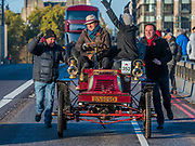 Another car breaks down passing over Westminster bridge and gets a push start from bystanders - The London to Brighton Veteran Car Run, which dates back to 1927, was founded to commemorate the Emancipation Run of 1896, which celebrated the new-found freedom of motorists granted by the 'repeal of the Red Flag Act.' The Act raised the speed limit to 14mph and abolished the need for a man carrying a red flag to walk ahead of the cars whenever they were being driven. It is the longest running motoring event in the world, this year has a French theme in honour of the country's contribution to motoring's early days. It is is organised by the Royal Automobile Club.