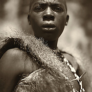 """""""The Bushman""""                                       Tanzania   <br /> I met this young Hadzabe Bushman in Tanzania. He wore the hide of a baboon, a sign of strength and hunting skills. I was never sure who was watching who. He had an intensity in his eyes,  a concentration,  a deep look of trying to understand who we were and why we were there. But I will never forget when we left.   I turned and looked at him as we walked away. He nodded his head and with a small smile gave me a wave as if to say, """"I will see you again."""""""