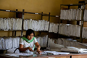 Computer generated designs A4 print-outs is being stuck together to 1:1 size for the weavers to work according to. <br /> Amity Factory does not employ children and is a licensee of the GoodWeave Foundation and their carpets carry the GWF label.The weavers work according to the design,printed on paper hanging above them. Most are women and many mothers and they work inthe factory 12-14 hours /day 6 days/week. The Good Weave Foundation is a charity set up in partnership with the Nepalese carpet industry. The aim is to eliminate child labor in all carpet factories in Nepal. Factories which do not employ children can sign up with the charity and become a licensee to the GWF brand and label their carpets with the GWF label which promises any buyers abroad that no children were involved in making the carpets.