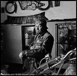 Suzuki, President Solo Angels MC. Tijuana, Mexico. 1995 <br /> <br /> Limited Edition Print from an edition of 50. Photo ©1995 Michael Lichter.<br /> <br /> The Story: Suzuki liked the glorified hogs, but not the pretentious attitudes of the riders. Although he had none of the trappings of his fellow riders; no money, no Harley, and limited budget for food and drink, he rode along. His nature was different though. He was wild, enjoyed a good drunk and a fistfight. He chased the women, and wore his rags with pride. He soon tired of the Road Angels style and quit. Ultimately he started his own club the Solo Angels. He worked odd jobs for six years and saved for his first and last Harley. In 1968 Suzuki bought a used Sportster and built his first chopper. He raked the frame, extended the front-end, built a set of long upswept fishtails and mounted them to a tall and sharp as a knife sissybar. He dug up the first coffin gas tank to be seen south of the border, bolted on a set of tall buckhorn handlebars and got the most radical paint job in the city. He set the ramshackle town on fire every time he blew through. After almost thirty years, he's still straddling the same machine with his colors. It has been his one and only, his true love. <br /> <br /> By K. Randall Ball, from an interview with Suzuki