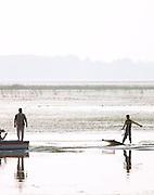 Local men waterski on Lake Dal, Kashmir, India