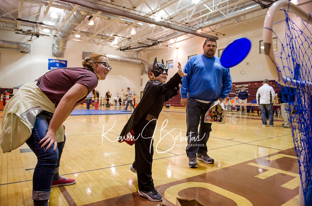 """Johanna Morris and Scott Canning watch as """"Batman"""" Brady Canning plays the Frisbee Game during Friday evenings Halloween Party at Gilford Middle School.  (Karen Bobotas/for the Laconia Daily Sun)"""
