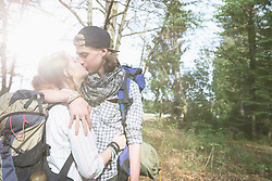 Young couple hiking with backpack and kissing in a forest, Bavaria, Germany