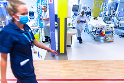 © Licensed to London News Pictures . 18/08/2021. Manchester , UK . A red line on the floor marks out a zone within which additional precautions to prevent the spread of transmissible illnesses must be deployed . Clinicians treat patients , many of whom are not conscious, for the effects of Coronavirus , on the Critical Care Ward at Manchester Royal Infirmary . Image pixelated at source as a condition of access. Photo credit : Joel Goodman/LNP