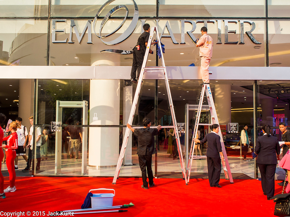"""27 MARCH 2015 - BANGKOK, THAILAND: Workers clean the front window for """"EmQuartier,"""" a new mall in Bangkok. """"EmQuartier"""" is across Sukhumvit Rd from Emporium. Both malls have the same corporate owner, The Mall Group, which reportedly spent 20Billion Thai Baht (about $600 million US) on the new mall and renovating the existing Emporium. EmQuartier and Emporium have about 450,000 square meters of retail, several hotels, numerous restaurants, movie theaters and the largest man made waterfall in Southeast Asia. EmQuartier celebrated its grand opening Friday, March 27.    PHOTO BY JACK KURTZ"""