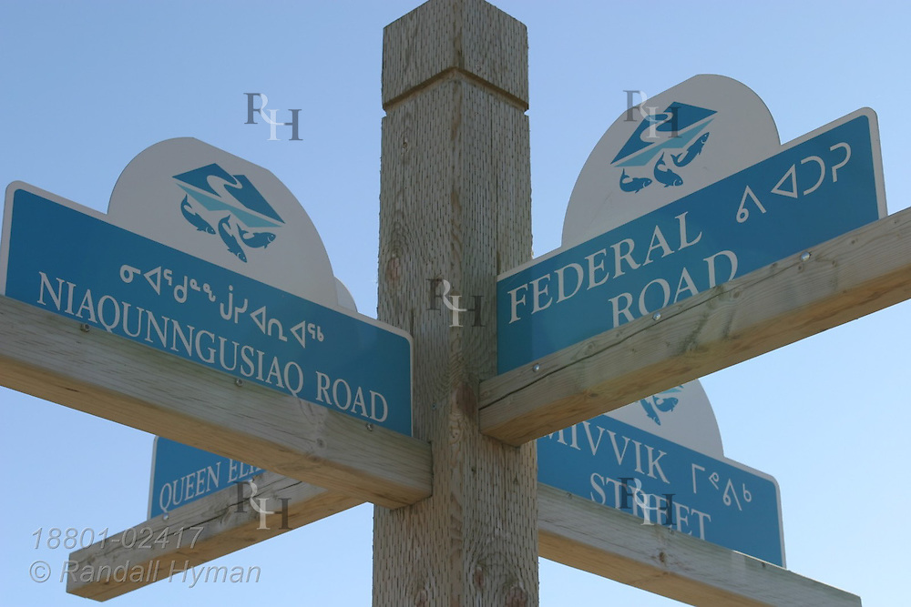 Sign post in capital city of Iqaluit features street names in English and Inuktitut, official languages of  the federal territory of Nunavut; Baffin Island, Canada