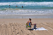 Israel, Haifa, Carmel Beach, Israelis go to the Beach to escape the heat. Teen sunbathing on the beach