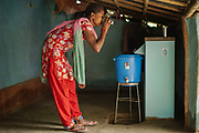 Manjali Hasda drinks clean water from the biosand water filter at her home in  Sharanamati Village, Nepal