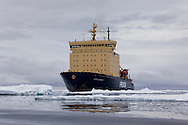The icebreaker Kapitan Khlebnikov waits out in icy waters as passengers venture towards Peter 1 Øy in Zodiacs.