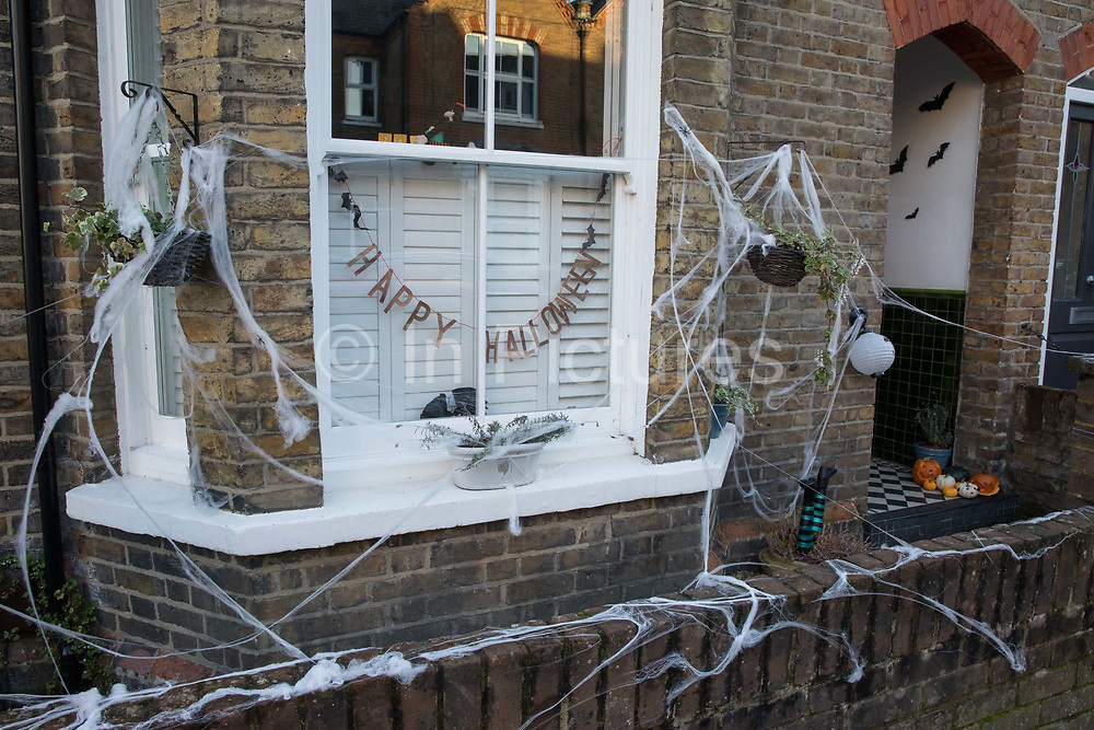Cobwebs and pumpkins are arranged around a garden to mark Halloween on 31 October 2020 in Windsor, United Kingdom. Halloween celebrations, and in particular the custom of trick-or-treating, will vary across the UK this year due to coronavirus restrictions which differ by Tier alert levels and the Prime Minister's official spokesman has urged people to apply common sense.