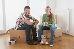 Couple taking a break from unpacking in their new home, Bavaria, Germany
