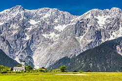 A chapel below the beautiful a limestone escarpment of the Austrian Alps in Wildermieming Austria.