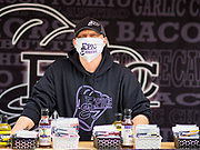 23 MAY 2020 - AMES, IOWA: BRANDON HEIDT, owner of Epic Eateries, wears a face mask in his tent at the Farmers' Market in downtown Ames. he sells spices, sauces, and dips. The Ames Main Street Farmers' Market reopened Saturday after nearly a month of only online sales because of Iowa's bans on large gatherings caused by the COVID-19 pandemic. Only about 15 venders set up stalls Saturday and attendance was significantly lower than normal. All of the venders wore face masks and many, but not all, of the shoppers wore face masks. Farmers' markets are popular community gatherings in Iowa, but they've been on hiatus since the Coronavirus (SARS-CoV-2) pandemic. At this time, Iowa farmers' markets are not allowed to have entertainment or sell non-food or non-agricultural goods.          PHOTO BY JACK KURTZ