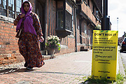 A woman passes a Covid-19 public information notice warning of the spread of the Delta variant on 14th July 2021 in Wokingham, United Kingdom. The leader of Wokingham Borough Council, John Halsall, has urged local residents to do all they can to avoid spreading the coronavirus as Covid-19 rates per 100,000 rise in the borough in advance of the planned lifting of national lockdown restrictions on 19th July.