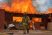 Capt. Jon Jelle of the Ventura County Fire Department walks away from the home after using an accelerant to set the house on fire during live fire training at the old Miller Horse Ranch on Oct. 27 in North Ranch.
