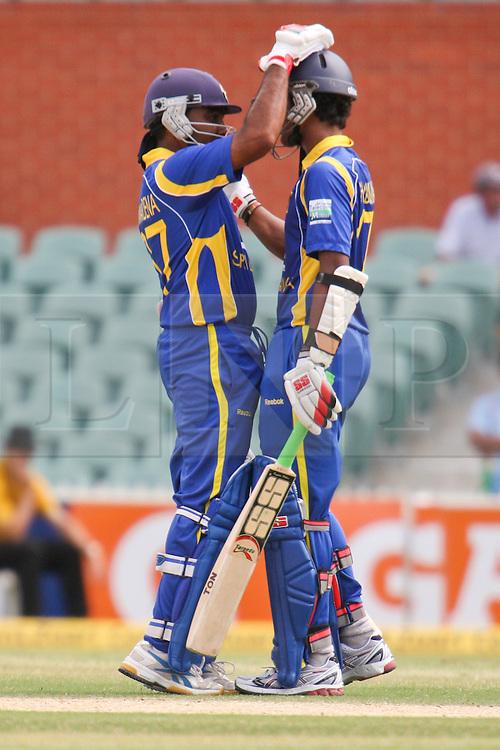 © Licensed to London News Pictures. 14/02/2012. Adelaide Oval, Australia. Sri Lankan batsman Dinesh Chandimal (left) is congratulated by his captain Mahela Jayawardena after making 50 during the One Day International cricket match between India Vs Sri Lanka. Photo credit : Asanka Brendon Ratnayake/LNP