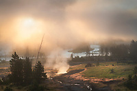 Fog and steam rising from Mud Volcano area geysers and hot springs at sunrise. Yellowstone National Park