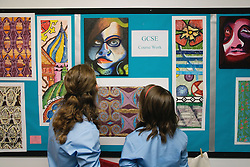 Secondary school students looking at an exhibition of GCSE artwork,