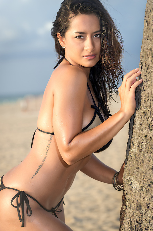 Seductive woman posing in a side view shot in the beach