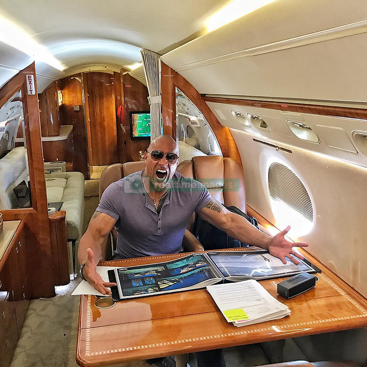"""Dwayne Johnson releases a photo on Instagram with the following caption: """"Homework hurts my brain. \nFor our movie #Skyscraper our art department created this stunning architectural design book that informs the look and tone of our film. \nFor consulting our script we spoke to world renowned architect, Adrian Smith who designed the world's current tallest structures -- Burj Khalifa in Dubai and the building that will surpass it, the Jeddah Tower in Jeddah, Saudi Arabia. \nFascinating to study this stuff.. how skyscrapers will continue to get taller, how that affects the neighborhood and ecosystem, how wind affects the architecture, wireless elevators etc. \nIn short think DIE HARD meets TOWERING INFERNO in the world's tallest skyscraper... in CHINA. \nI'm just mad because those bastards in the art department didn't make this a pop up book. #Homework #Skyscraper #Vancouver #China"""". Photo Credit: Instagram *** No USA Distribution *** For Editorial Use Only *** Not to be Published in Books or Photo Books ***  Please note: Fees charged by the agency are for the agency's services only, and do not, nor are they intended to, convey to the user any ownership of Copyright or License in the material. The agency does not claim any ownership including but not limited to Copyright or License in the attached material. By publishing this material you expressly agree to indemnify and to hold the agency and its directors, shareholders and employees harmless from any loss, claims, damages, demands, expenses (including legal fees), or any causes of action or allegation against the agency arising out of or connected in any way with publication of the material."""