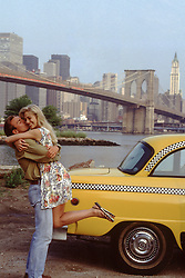 man holding a woman in his arms and kissing near a taxi in New York City