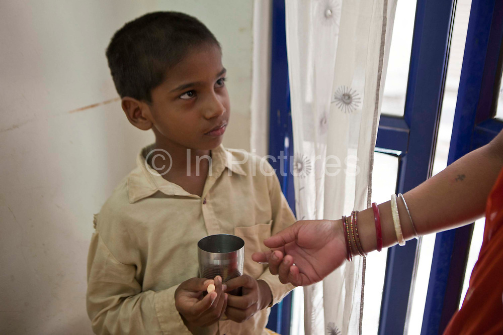 An 8 year old Indian boy is given his daily medication tablets for Tuberculosis (TB) which are being dispensed to him by a Directly Observed Therapy (DOT) worker.  The treatment for TB is a minimum 6 month course of combination antibiotics that must been taken everyday, otherwise fatal drug resistance can develop.  The medication is free and provided by the government. TB is an infectious disease and a huge public health issue often associated with poverty.  TB is completely curable, however TB rates are increasing and India suffers from the highest burden of TB in the world.  Health clinic in Tehkhand Slum, Delhi, India.