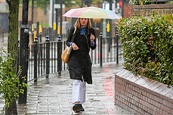 © Licensed to London News Pictures. 18/06/2021. London, UK. A woman shelters from the rain underneath an umbrella in north London, as wet weather conditions continue after a warm dry spell. Photo credit: Dinendra Haria/LNP